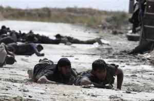 Free Syrian Army fighters take cover from snipers by crawling on the front line in Aleppo's Sheikh Saeed neighbourhood