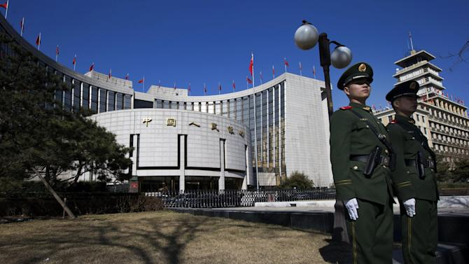FILE - In this Wednesday, March 13, 2013 file photo, Chinese paramilitary policemen stand on duty outside the People's Bank of China in Beijing, China. Pressures appeared to ease somewhat on Friday, June 21, 2013 as the key interbank lending rate dropped slightly, prompting speculation that the central bank had intervened, possibly through open market operations, to inject more funds into the system. The People's Bank of China generally does not comment on its market activities. (AP Photo/Ng Han Guan, File)