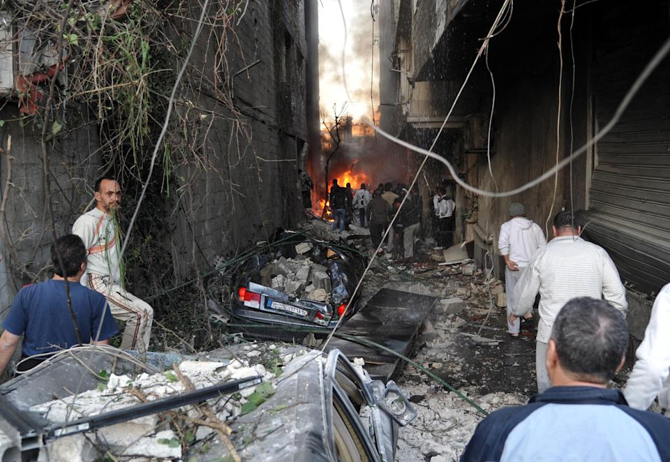 In this photo released by the Syrian official news agency SANA, Syrian citizens gather at an alley destroyed by two cars bombs, at Jaramana neighborhood, in the suburb of Damascus, Syria, Wednesday, Nov. 28, 2012. (AP Photo/SANA)