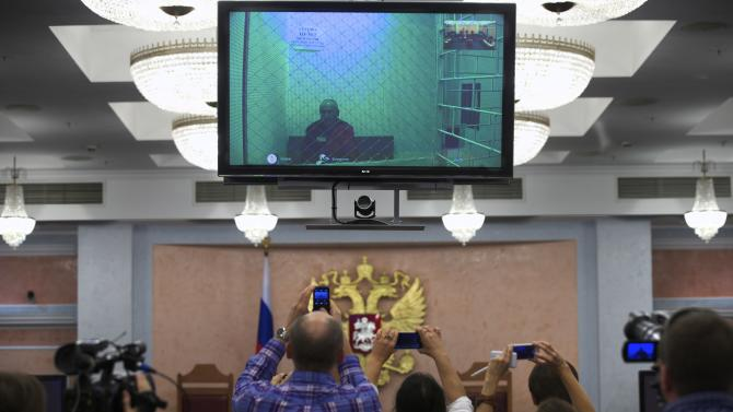Journalists take pictures as jailed oil tycoon Mikhail Khodorkovsky speaks from his prison colony via a video link broadcast to the Supreme Court in Moscow, Russia, Tuesday, Aug. 6, 2013. The Supreme Court considers former Yukos CEO Khodorkovsky's appeal to overturn his 2010 conviction.(AP Photo/Alexander Zemlianichenko)