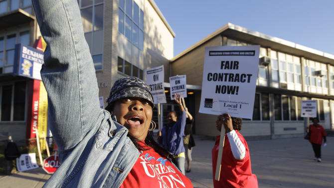 Chicago teachers walk a picket line outside Benjamin Banneker Elementary School in Chicago, Monday, Sept. 10, 2012, after they went on strike for the first time in 25 years. Union and district officials failed to reach a contract agreement despite intense weekend negotiations. (AP Photo/M. Spencer Green)