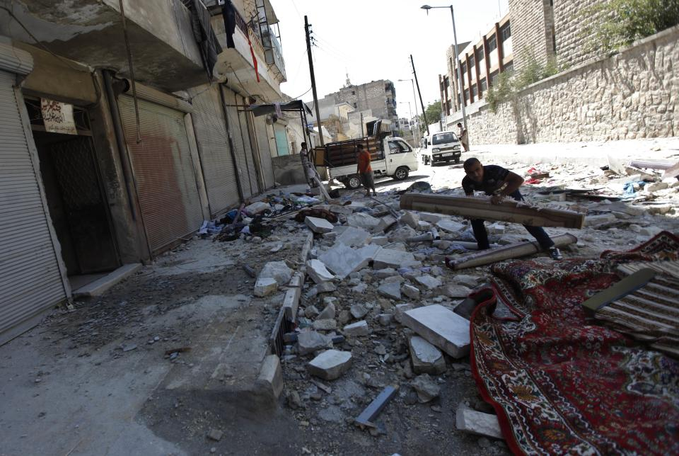 A Syrian man salvages what he can from his belongings after his house was hit during a Syrian government airstrike in Aleppo, Syria, Sunday, Aug. 19, 2012 (AP Photo/ Khalil Hamra)