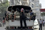 Syrian rebels patrol a neighbourhood in the northern city of Aleppo