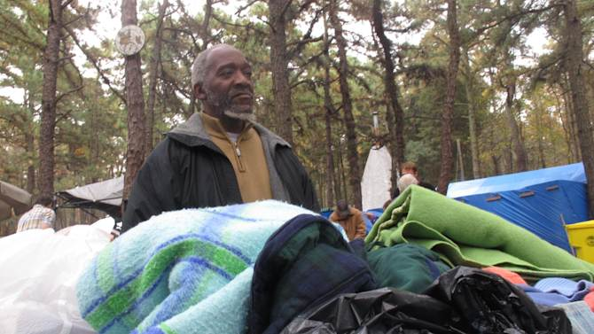 "In this Oct. 24, 2012 photo, Gregory ""Pops"" Maple, one of three representatives chosen by members of a homeless encampment in Lakewood N.J. to represent their interests during an election in October, sorts through donated clothing at the camp.The camp was declared officially closed on June 30, 2014 when the last of its 120 occupants was given temporary housing.(AP Photo/Wayne Parry)"
