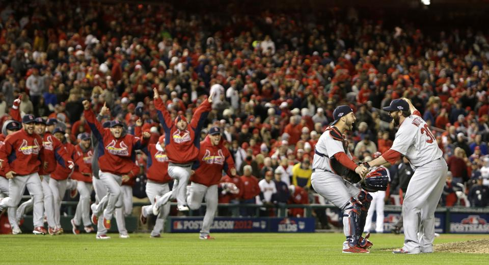 Cardinals closer Jason Motte (right) embraces catcher Tony Cruz as their teammates rush the field after Game 5 of the National League Division Series between the St. Louis Cardinals and the Washington Nationals on Friday, Oct. 12, 2012, at Nationals Park in Washington, D.C. (AP Photo/Chris Lee, Post Dispatch)