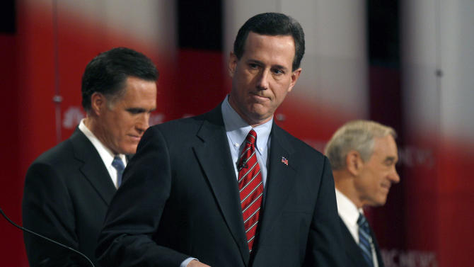 Former Pennsylvania Sen. Rick Santorum, center, walks of the stage after a Republican presidential candidate debate at the Capitol Center for the Arts in Concord, N.H., Sunday, Jan. 8, 2012. Former Massachusetts Gov. Mitt Romney, left, and Rep. Ron Paul, R-Texas are seen in the background.  (AP Photo/Charles Krupa)
