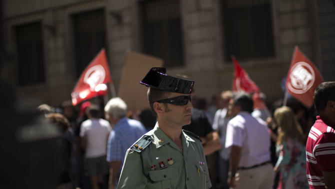 """A Guardia Civil member stands guard as civil servants march condemning the recent austerity measures announced by the Spanish government, during a demonstrations in Madrid, Spain, on Friday July 13, 2012.  Spanish civil servants, some dressed in the black of mourning, took to the streets Friday to protest their second wave of wage cuts in as many years as the government prepared to approve austerity measures that include those reductions as part of a deficit-cutting plan to save euro 65 billion through 2015. Placards read in Spanish """"down with tax fraud amnesty"""". (AP Photo/Emilio Morenatti)"""