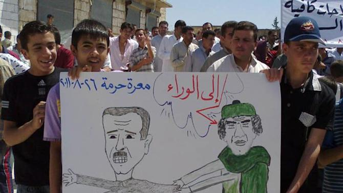 "In this citizen journalism image made on a mobile phone and provided by Shaam News Network, anti-Syrian President Bashar Assad protesters, hold a cartoon placard depicting Moammar Gadhafi, right, and Syrian President Bashar Assad, left, with Arabic words read:""step back,"" during a demonstration against the Syrian regime, at Maaret Harma village, in Edlib province, Syria, on Friday Aug. 26, 2011. Syrian security forces killed at least two people as tens of thousands of anti-government protesters flooded the streets on the last Friday of the holy month of Ramadan, a time that many activists hoped would become a turning point in the uprising. (AP Photo/Shaam News Network) EDITORIAL USE ONLY, NO SALES, THE ASSOCIATED PRESS IS UNABLE TO INDEPENDENTLY VERIFY THE AUTHENTICITY, CONTENT, LOCATION OR DATE OF THIS HANDOUT PHOTO"
