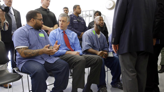 Education Secretary Arne Duncan, second from left, speaks with inmate Terrell Johnson, a participant in the Goucher College Prison Education Partnership at Maryland Correctional Institution-Jessup, Friday, July 31, 2015, in Jessup, Md. After a roundtable discussion at the prison, the Education Department announced Friday that it would conduct a limited pilot program to give prisoners access to the Pell grants, allowing them to take college courses behind bars. (AP Photo/Patrick Semansky)