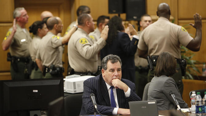 Baliffs are sworn in to protect the jury as Brian Panish, foreground, attorney for the Michael Jackson family waits in a downtown Los Angeles courtroom, Thursday, Sept. 26, 2013. Katherine Jackson's negligence lawsuit against concert promoter AEG Live LLC has gone to the jury. (AP Photo/Los Angeles Times, Al Seib, Pool)