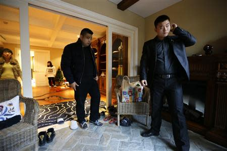 Bodyguard Han, who was hired from Tianjiao Special Guard/Security Consultant, checks his earphone as his employer Zhang prepares to leave home on the outskirts of Beijing