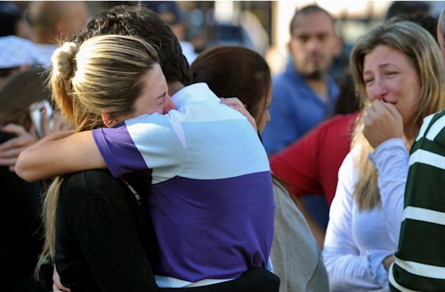 Relatives of victims react near the Kiss nightclub in Santa Maria city,  Rio Grande do Sul state, Brazil, Sunday, Jan. 27, 2013.  According to police more than 200 died in the devastating nightclub fi