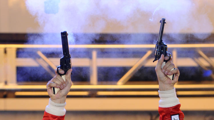 Justin Wilson, of England, fires blanks from a two revolvers in victory lane after winning the IZOD IndyCar Firestone 550 auto race at Texas Motor Speedway, Saturday, June 9, 2012, in Fort Worth, Texas. (AP Photo/Ralph Lauer)