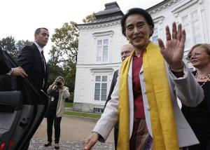 Myanmar's opposition leader Suu Kyi waves after her meeting with former Polish president Walesa in Warsaw