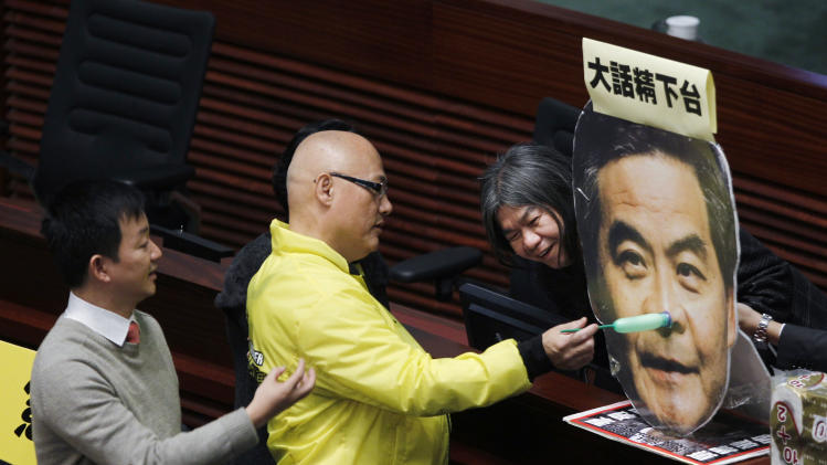 "Hong Kong pro-democracy lawmakers from right, Leung Kwok-hung, Albert Chan and Raymond Wong set up a cutout of the head of Chief Executive Leung Chun-ying with ""Pinocchio's nose"" and a sign which reads ""Liar steps down"" before Chief Executive Leung Chun-ying delivering his policy address at the Legislative Council in Hong Kong Wednesday, Jan. 16, 2013. Leung Chun-ying focused on the social problems such as housing, pollution and economic development for the next five years. (AP Photo/Kin Cheung)"