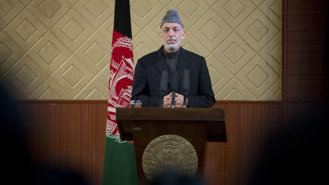 """Afghan President Hamid Karzai pauses during a ceremony at Kabul University in Kabul, Afghanistan, Thursday, May 9, 2013. Karzai said he is ready to let the U.S. have nine bases in the country after the 2014 combat troop pullout, but wants Washington's """"security and economic guarantees"""" first.  (AP Photo/Anja Niedringhaus)"""