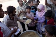 Syrian refugees receive food from a makeshift kitchen in a temporary refugee camp near the Al-Salama crossing between Syrian and Turkey
