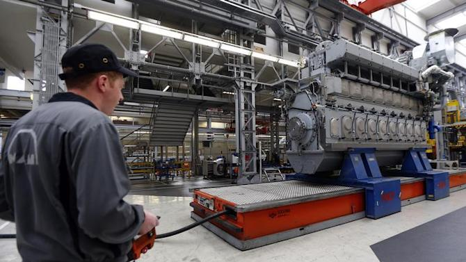 Workers assemble a large Diesel engine at the MAN Diesel & Turbo factory in Augsburg