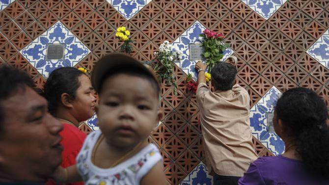 Relatives place flowers next their family plaque at a wave-shaped tsunami monument for victims of the 2004 tsunami in Ban Nam Khem