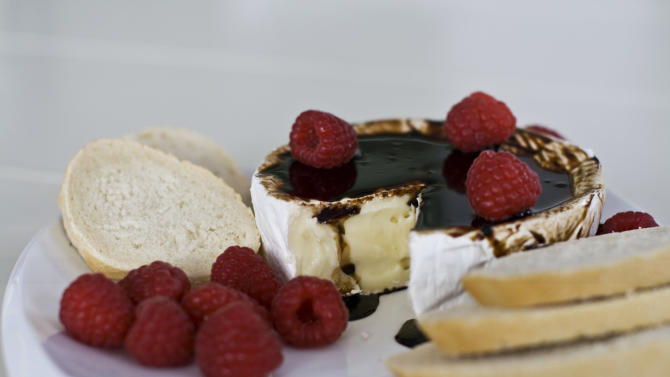In this image taken on Monday, November 26, 2012, brie with bourbon-balsamic glaze is shown on a platter in Concord, N.H. (AP Photo/Matthew Mead)