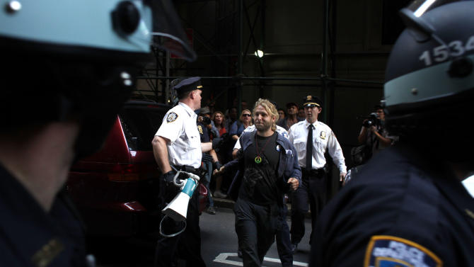 A man is led away during an Occupy Wall Street march, Monday, Sept. 17, 2012, in New York. A handful of Occupy Wall Street protestors were arrested during a march on the New York Stock Exchange on the anniversary of the grass-roots movement. (AP Photo/Jason DeCrow)