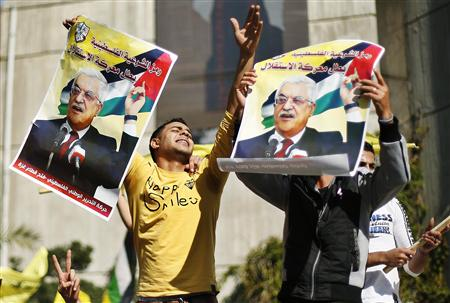 Palestinians hold posters of President Abbas during a rally in support of Abbas's efforts to secure a diplomatic upgrade at the U.N. in Gaza