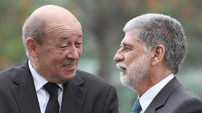 Brazil's Defense Minister Celso Amorim, right, talks with France's Defense Minister Jean-Ives Le Drian during a welcome ceremony at Brazil's Defense Ministry in Brasilia, Brazil, Monday, Nov. 5, 2012. Le Drian is on a two-day official visit to Brazil.  (AP Photo/Eraldo Peres)