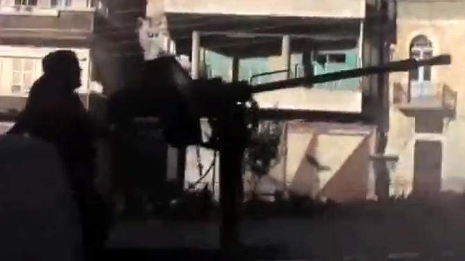 In this Wednesday, Sept. 4, 2013 image taken from video obtained from the Shaam News Network, which has been authenticated based on its contents and other AP reporting, a Free Syrian army fighter during clashes with government forces, unseen, in Maaloula, western Syria. Syrian government troops battled al-Qaida-linked rebels over a regime-held Christian village in western Syria for the second day Thursday, as world leaders gathered in Russia for an economic summit expected to be overshadowed by the prospect of U.S.-led strikes against the Damascus regime. Residents of Maaloula said the militants entered the village late Wednesday, Sept. 4,2013. (AP Photo/Shaam News Network via AP video)