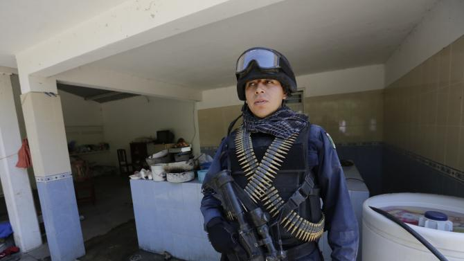 "A federal police officer stands guard inside one of the ranches where Servando ""La Tuta"" Gomez lived, during a media tour near the town of Uruapan in Michoacan state"
