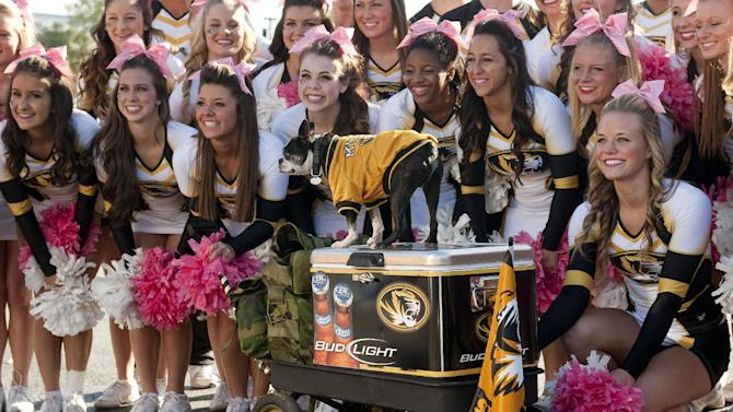The Missouri cheerleaders pose with Rommel the dog before the start of an NCAA college football game against South Carolina, Saturday, Oct. 26, 2013, in Columbia, Mo