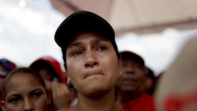 A woman cries as she waits to see the body of Venezuela's late President Hugo Chavez at the military academy where his body is lying in state in Caracas, Venezuela, Thursday, March 7, 2013. While Venezuela remains deeply divided over the country's future, the multitudes who reached the president's coffin were united in grief and admiration for a man many considered a father figure.   (AP Photo/Ariana Cubillos)