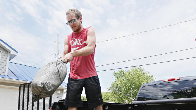 Colby Grant, of Jefferson, tosses sand bags from a truck bed as he helps his father, Dennis Johnson, prepare his home for flooding in McCook Lake, S.D., on Thursday, June 19, 2014. People along the river were working to battle record flooding. (AP Photo/Sioux City Journal, Dawn J. Sagert)