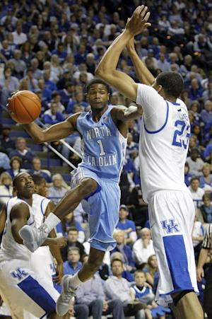 North Carolina's Dexter Strickland, left, looks for a teammate as Kentucky's Anthony Davis, right, and Marquis Teague defend during the first half of an NCAA college basketball game in Lexington, Ky., Saturday, Dec. 3, 2011. (AP Photo/James Crisp)
