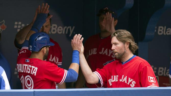 Toronto Blue Jays Jose Bautista, left, is congratulated by starting pitcher R.A. Dickey, right, after scoring on a J.P Arencibia single during the third inning of a baseball game against the Detroit Tigers in Toronto, on Monday July 1, 2013. (AP Photo/The Canadian Press, Frank Gunn)