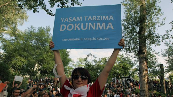 "A woman holds up a banner that reads ""Don't interfere with my life style "" as thousands of people gather in support of demonstrators staging a sit-in to prevent the uprooting of trees at an Istanbul park, in Ankara, Turkey, Friday, May 31, 2013. Riot police clash with demonstrators after they used tear gas and pressurized water in a dawn raid on Friday to rout a peaceful demonstration by thousands of people in Istanbul. Several protesters were injured when a wall they climbed collapsed during a police chase. Police moved in to disperse the crowd on the fourth day of the protest against a government plan to revamp Istanbul's main square, Taksim. (AP Photo/Burhan Ozbilici)"