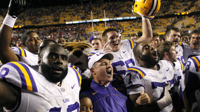 LSU head coach Les Miles sing the school anthem with his team, including defensive tackle Bennie Logan (18) and defensive tackle Josh Downs (77) in the second half of their NCAA college football game against Mississippi in Baton Rouge, La., Saturday, Nov. 17, 2012. LSU won 41-35. (AP Photo/Gerald Herbert)