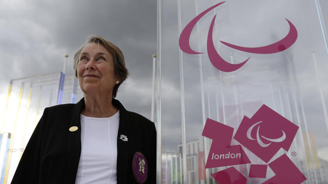 In this Thursday, Aug. 23, 2012 photo, Eve Loeffler, daughter of the founder Paralympic games Ludwig Guttman, stands by the logo of the Paralympic Games at the athletes village at the Paralympic park. The Olympics have Baron Pierre de Coubertin, the founder of the modern games. The Paralympics have Sir Ludwig Guttmann. Guttmann, a Jewish neurosurgeon who fled Nazi Germany, pioneered athletic competition as therapy for patients with spinal injuries and organized an archery competition for 16 patients at Britain's Stoke Mandeville hospital in 1948. From this humble start have come the Paralympic Games, which this week will bring more than 4,000 athletes from around the world to London. (AP Photo/Alastair Grant)