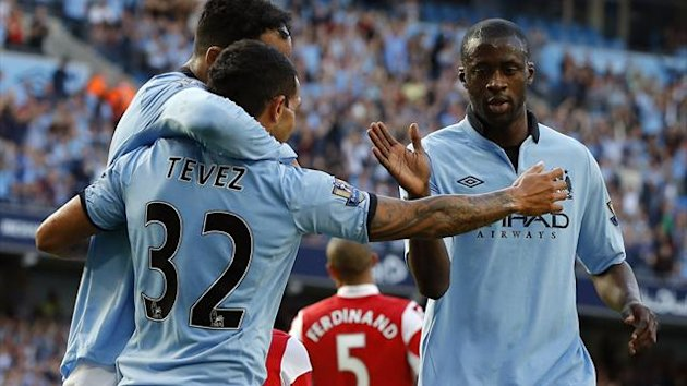 Manchester City's Yaya Toure (R) celebrates his goal against Queens Park Rangers with teammates Carlos Tevez