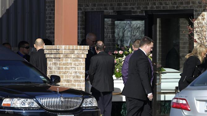 The casket of Kasandra Perkins is rolled out of the Ridgeview Family Fellowship Church as mourners stand by following a funeral service, Thursday, Dec. 6, 2012, in Blue Ridge, Texas.  Perkins was shot and killed last Saturday by her boyfriend Jovan Belcher, a Kansas City Chiefs football player. AP Photo/Tony Gutierrez)