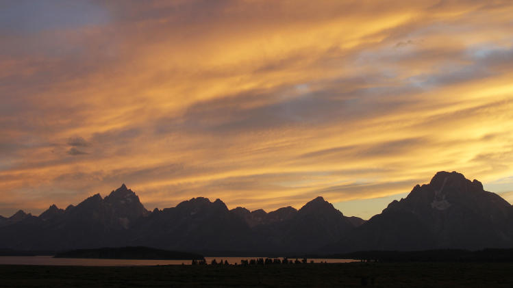 The sun sets behind the Teton Mountains as viewed from the Jackson Lake Lodge, where Federal Reserve Chairman Ben Bernanke is attending the Jackson Hole Economic Symposium, Thursday, Aug. 30, 2012, at Grand Teton National Park near Jackson Hole, Wyo. (AP Photo/Ted S. Warren)