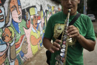 "In this Dec. 11, 2012 photo, Oscar Molina plays a saxophone that was repaired with recycled materials outside the school where he practices with ""The Orchestra of Instruments Recycled From Cateura"" in Cateura, a vast landfill outside Paraguay's capital of Asuncion, Paraguay. The community of Cateura could not be more marginalized. But the music coming from garbage has some families believing in a different future for their children. (AP Photo/Jorge Saenz)"
