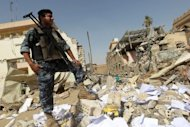 An Iraqi policeman inspects the damage following a bomb attack on the Shiite endowment headquarters in central Baghdad. Iraqi leaders appealed for calm after a suicide bomber killed 25 people at a Shiite foundation&#39;s offices in Baghdad, sparking fears of sectarian strife at a time of political crisis