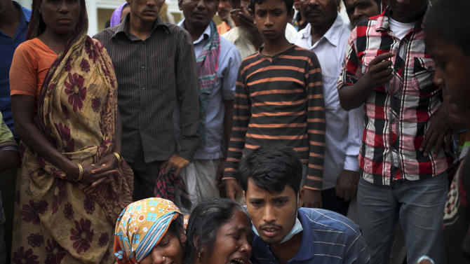 A woman is comforted as she grieves after identifying the body of her daughter, a victim of the garment factory collapse, Sunday, May 5, 2013 in Savar, near Dhaka, Bangladesh. The death toll from the collapse of a shoddily built garment-factory building in Bangladesh continued its horrifying climb, reaching 580 on Sunday with little sign of what the final number will be. The disaster is likely the worst garment-factory accident ever, and there have been few industrial accidents of any kind with a higher death toll.(AP Photo/Wong Maye-E)
