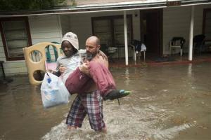 Charles Davidson helps his neighbor Santonio Coleman, 11, from his flooded home in the Kelly Ave. Basin area of Pensacola
