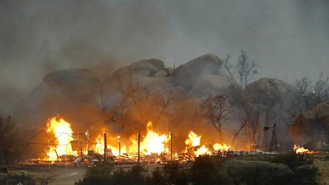 Homes burn as the Yarnell Hill Fire burns in Glenn Ilah on Sunday, June 30, 2013 near Yarnell, Ariz. The fire started Friday and picked up momentum as the area experienced high temperatures, low humidity and windy conditions. It has forced the evacuation of residents in the Peeples Valley area and in the town of Yarnell. (AP Photo/The Arizona Republic, David Kadlubowski)
