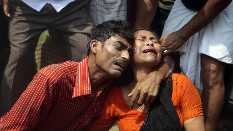 Relatives mourn a victim at the site after an eight-story building housing several garment factories collapsed in Savar, near Dhaka, Bangladesh, Wednesday, April 24, 2013. Dozens were killed and many more are feared trapped in the rubble. (AP Photo/ A.M. Ahad)