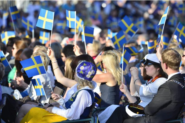 People in the audience wave Swedish flags during the traditional National Day celebrations with the royal family at Skansen in Stockholm