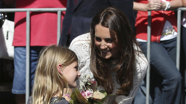 Britain's Kate, the Duchess of Cambridge, right, smiles while talking with a young girl during a tour of the Sydney Easter Show in Sydney, Friday, April 18, 2014. (AP Photo/Rick Rycroft)