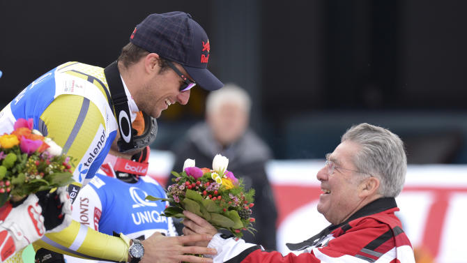 Norway's gold medal winner Aksel LundSvindal receives flowers by Austrian President Heiny Fischer, right, after the men's downhill  at the Alpine skiing world championships in Schladming, Austria, Saturday, Feb. 9, 2013. (AP Photo/Kerstin Joensson)