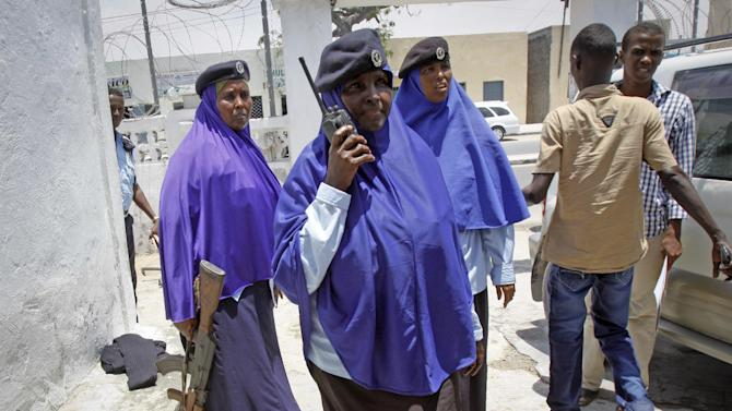 In this photo taken Sunday, March 30, 2014, a female Somali soldier talks on her walkie-talkie outside a police station in Mogadishu, Somalia. It's unusual to see a female in the military in traditionally conservative Somali society where women's duties are generally at home and limited to family chores, but determined women are breaking down those barriers with about 1,500 females now in the military of 20,000, according to estimates. (AP Photo/Farah Abdi Warsameh)
